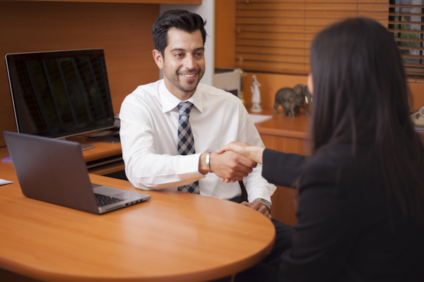 A male lawyer meeting with a female client in a small office space.